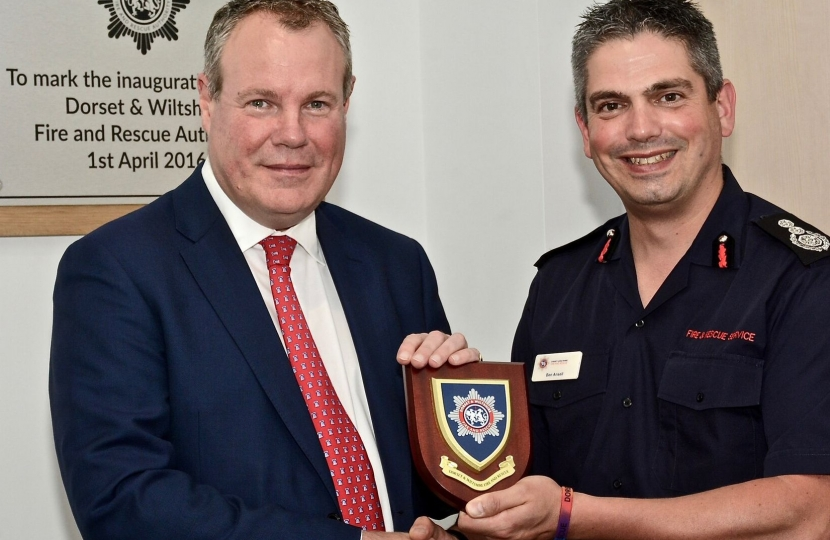 Dorset & Wiltshire Fire Chief Ben Ansell presenting Conor with the shield of the new fire service.