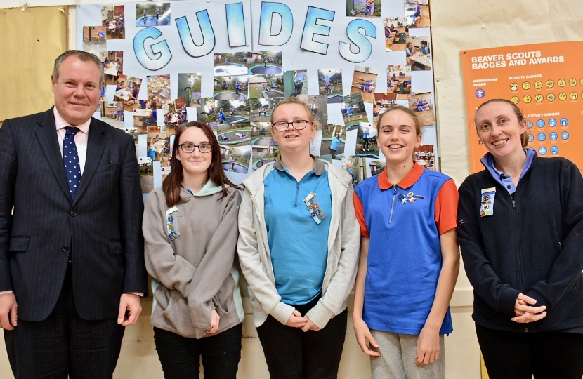 Conor pictured with the Girl Guides in front of their activities board.
