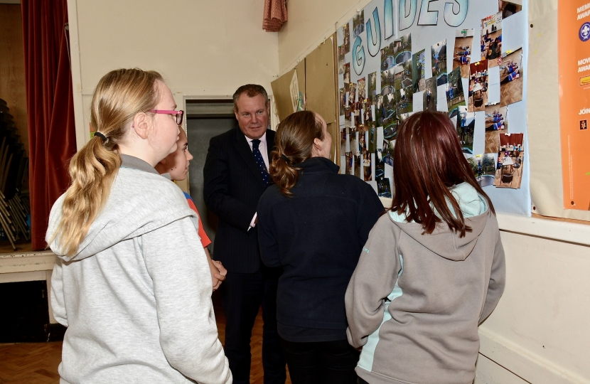 Conor pictured being shown pictures of former activities by the Girl Guides.