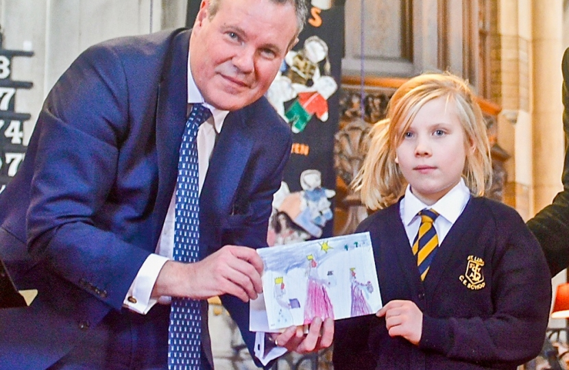 Conor with Charlotte Crowe from St Luke's School, Winton, and her winning design from Conor's Christmas Card Competition 2017 in print.