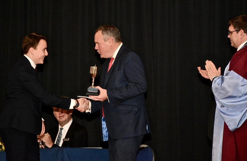 Conor pictured presenting a student with an award for academic excellence.