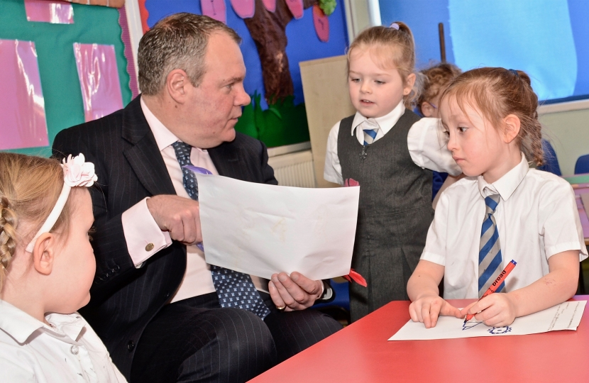 Conor pictured being shown a drawing by a student at Talbot Primary.