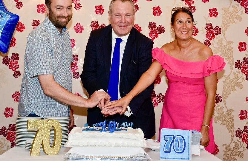 Conor cutting the cake with Sarah England and Matthew Moore.